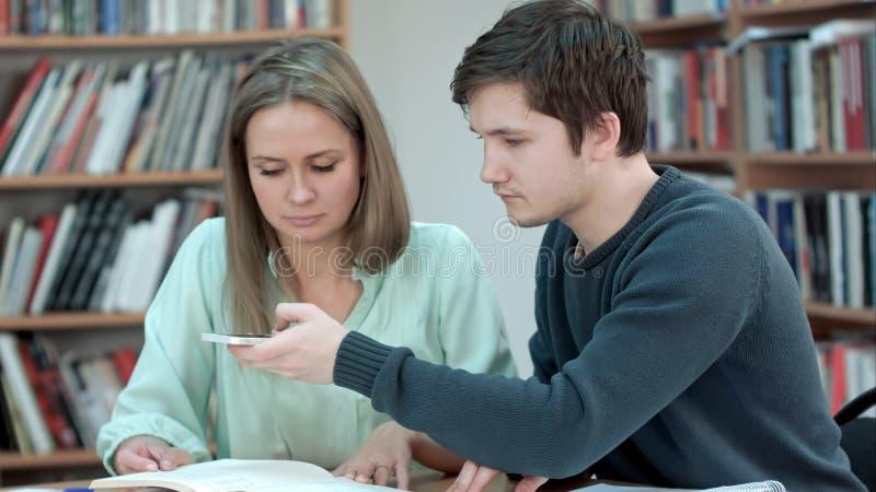 Giovani coppie che prendono una foto del libro in biblioteca immagini stock