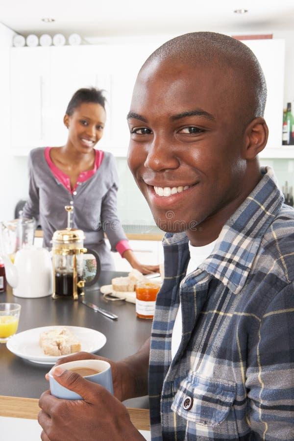 Giovani coppie che preparano prima colazione in cucina moderna fotografia stock