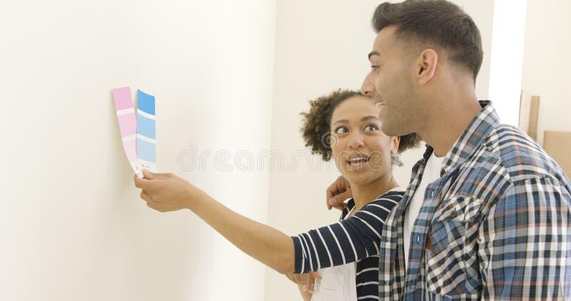 Giovani coppie che provano a scegliere un colore della pittura fotografia stock