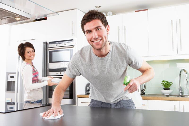 Giovani coppie che puliscono cucina moderna fotografie stock