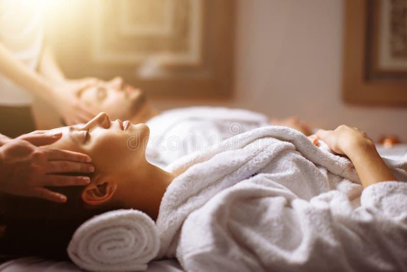 Giovani coppie che ricevono massaggio capo alla stazione termale di bellezza fotografie stock