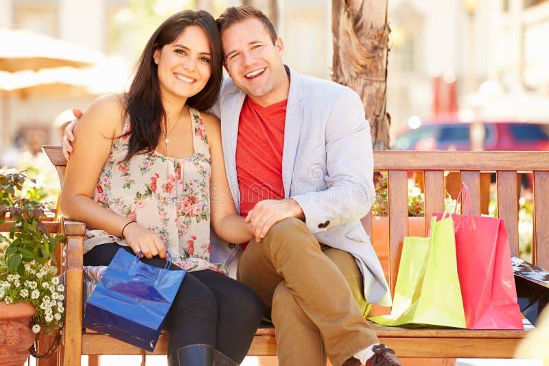 Giovani coppie che riposano con i sacchetti della spesa che si siedono nel centro commerciale fotografie stock libere da diritti