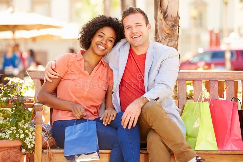 Giovani coppie che riposano con i sacchetti della spesa che si siedono nel centro commerciale fotografia stock