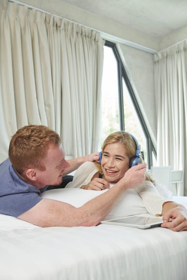 Giovani coppie che riposano sul letto immagini stock
