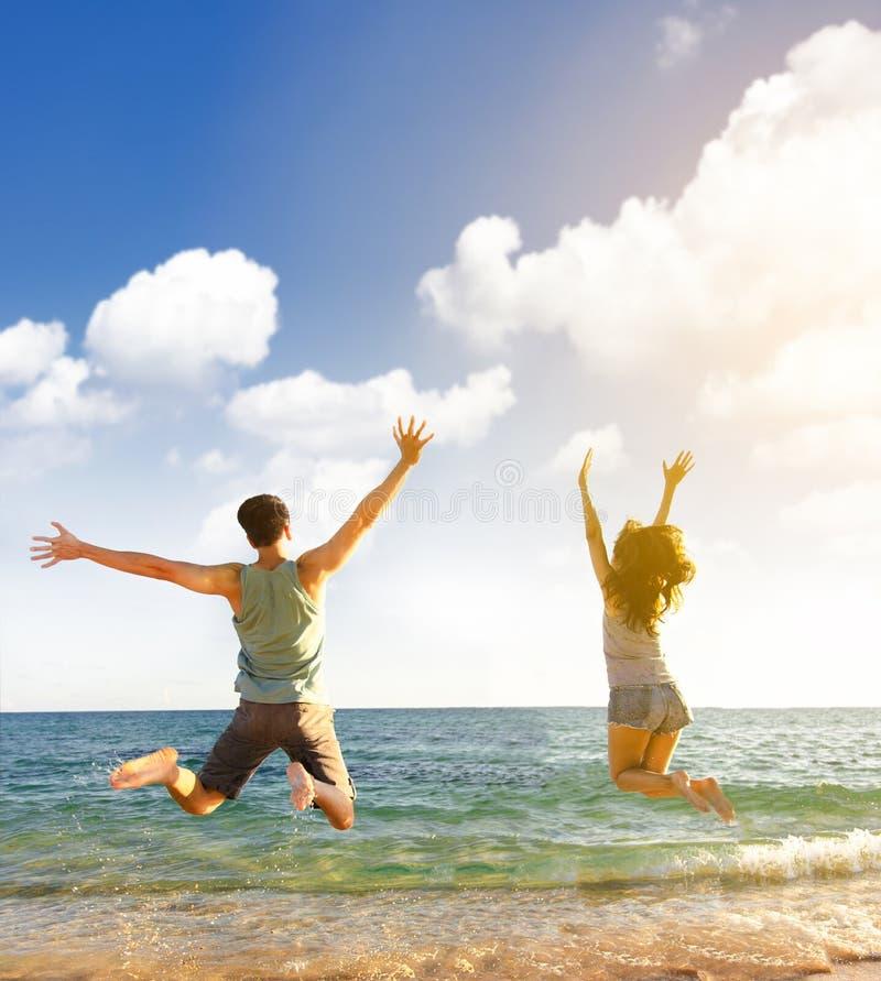 Giovani coppie che saltano sulla spiaggia immagine stock libera da diritti