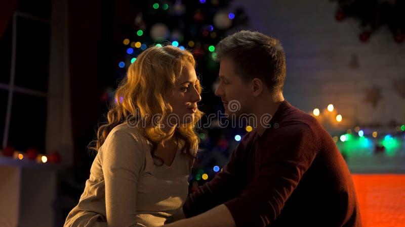 Giovani coppie che si innamorano sulla notte di Natale magica, atmosfera festiva, romanzesca fotografia stock
