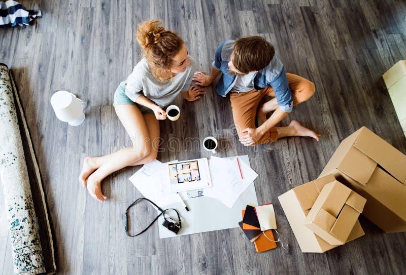 Giovani coppie che si muovono nella nuova casa, caffè bevente fotografia stock