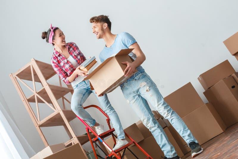 Giovani coppie che si muovono verso la nuova condizione della donna del posto sulla scala che mette i libri nella risata della sc fotografie stock libere da diritti