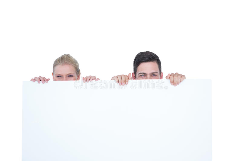 Giovani coppie che si nascondono dietro un segno in bianco immagine stock libera da diritti