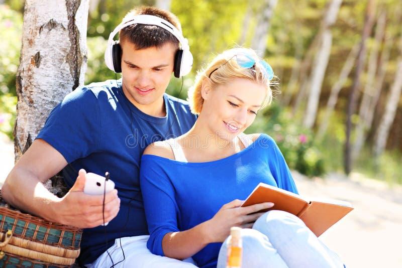 Giovani coppie che si rilassano alla spiaggia immagine stock libera da diritti