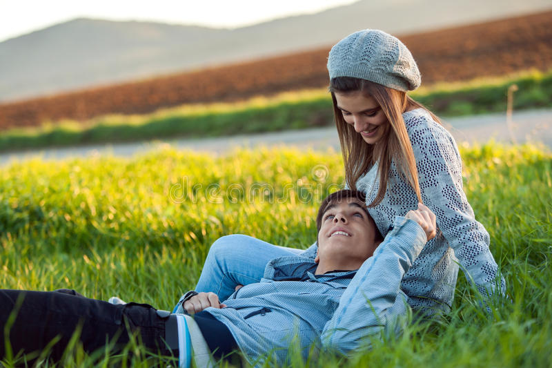 Giovani coppie che si rilassano nel campo di erba verde. fotografie stock