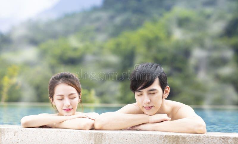 Giovani coppie che si rilassano in sorgenti di acqua calda immagini stock libere da diritti