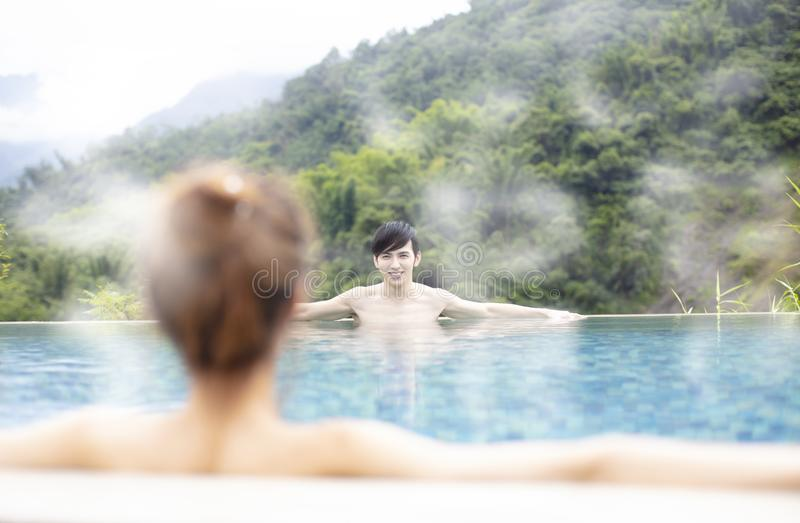 Giovani coppie che si rilassano in sorgenti di acqua calda fotografia stock