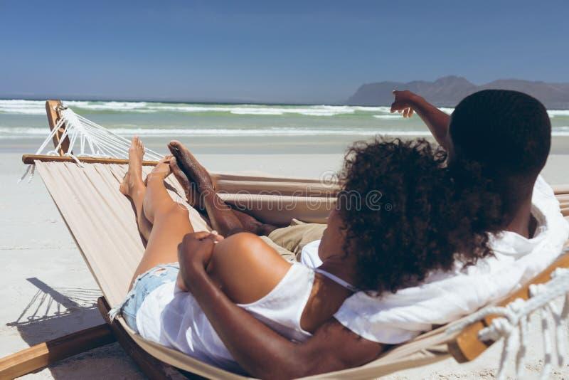 Giovani coppie che si rilassano sull'amaca alla spiaggia immagini stock libere da diritti