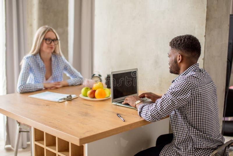 Giovani coppie che si siedono alla tavola e che lavorano con un computer portatile ed i documenti immagini stock libere da diritti