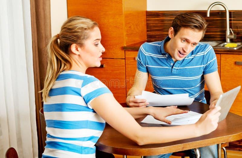 Giovani coppie che si siedono allo scrittorio e che cercano i piani di nuova casa fotografia stock libera da diritti