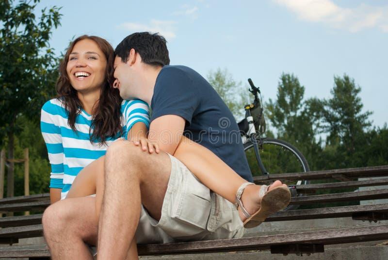 Giovani coppie che si siedono su un banco fotografie stock