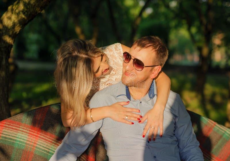 Giovani coppie che si siedono sul banco del giardino fotografie stock libere da diritti
