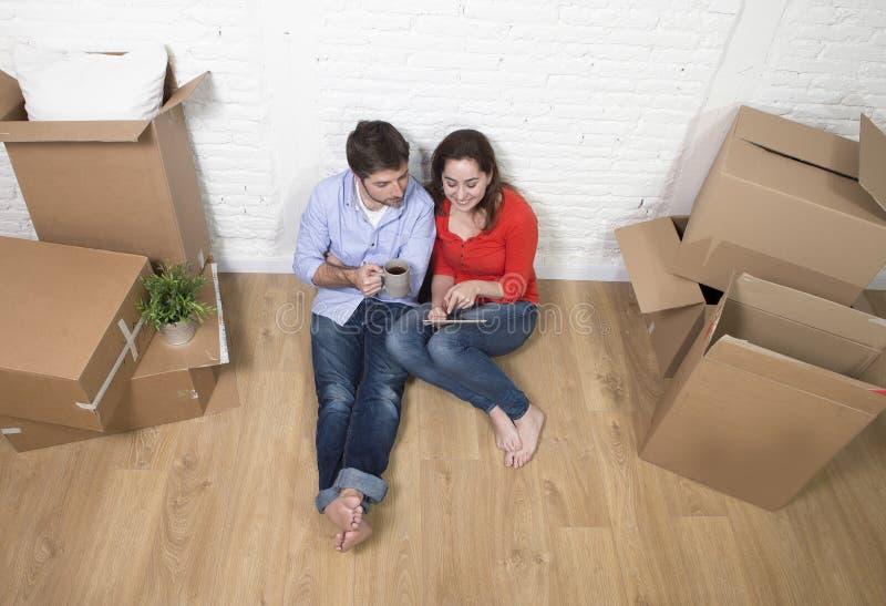 Giovani coppie che si siedono sul pavimento che si muove nella nuova casa facendo uso del cuscinetto digitale della compressa fotografia stock libera da diritti