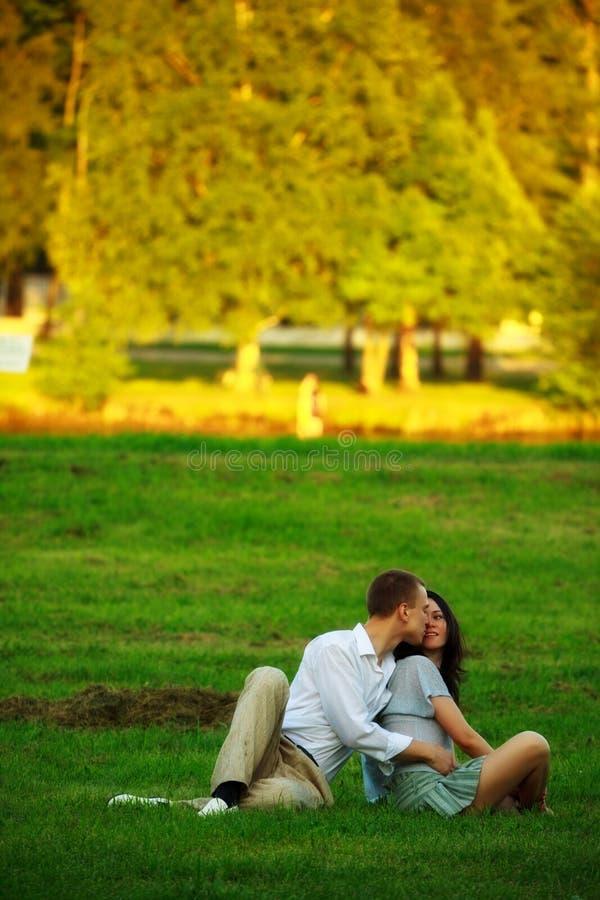 Giovani coppie che si siedono sul prato inglese della sosta immagine stock