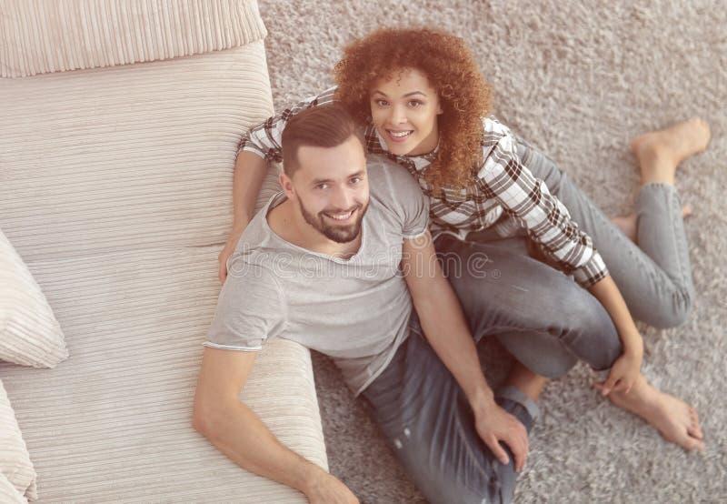 Giovani coppie che si siedono sul tappeto nel nuovo salone fotografie stock