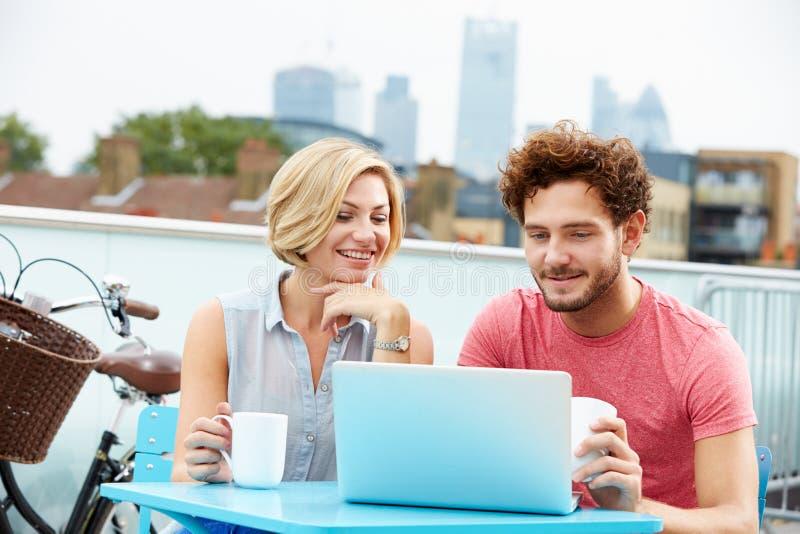 Giovani coppie che si siedono sul terrazzo del tetto facendo uso del computer portatile immagini stock libere da diritti