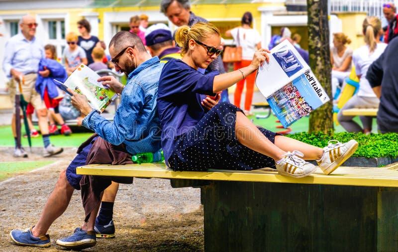 Giovani coppie che si siedono sul viaggio di pianificazione del banco della città alle riviste di viaggio della lettura dell'Ital fotografia stock