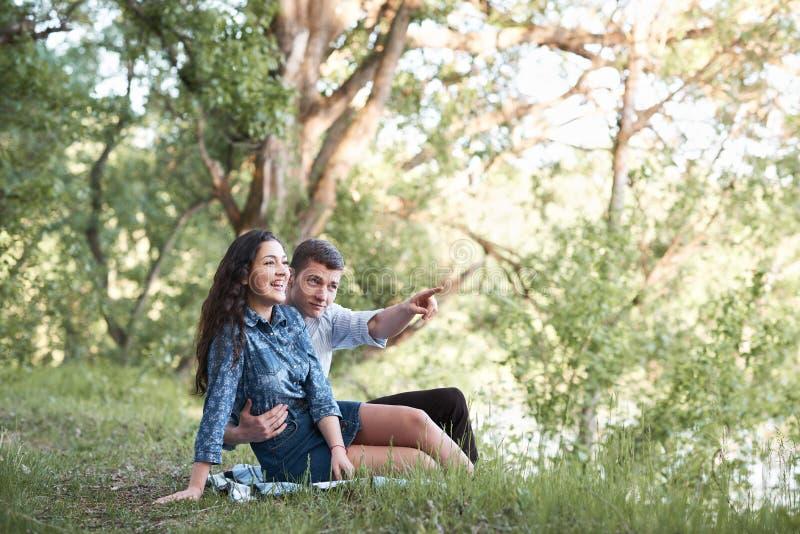 Giovani coppie che si siedono sull'erba nella foresta e che considerano tramonto, la natura di estate, luce solare luminosa, le o fotografia stock libera da diritti