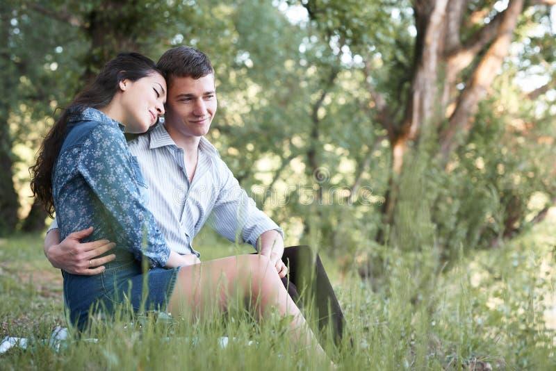Giovani coppie che si siedono sull'erba nella foresta e che considerano tramonto, la natura di estate, luce solare luminosa, le o immagine stock libera da diritti