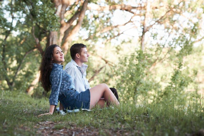 Giovani coppie che si siedono sull'erba nella foresta e che considerano tramonto, la natura di estate, luce solare luminosa, le o fotografie stock
