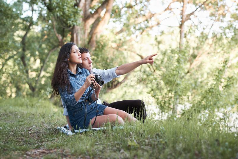 Giovani coppie che si siedono sull'erba nella foresta, prendenti le foto e considerare tramonto, natura di estate, luce solare lu fotografia stock libera da diritti