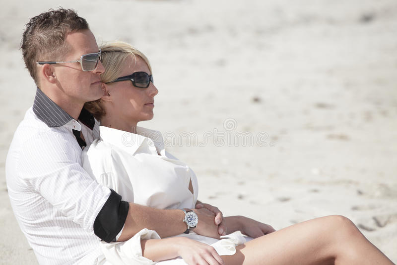 Giovani coppie che si siedono sulla sabbia fotografie stock libere da diritti