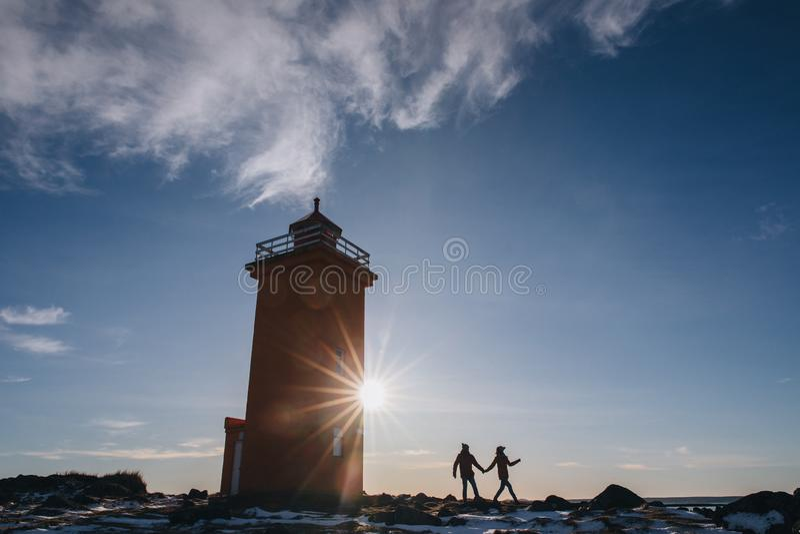 giovani coppie che si tengono per mano e che camminano vicino al faro in Islanda, reykjanes, stafnesviti fotografia stock libera da diritti