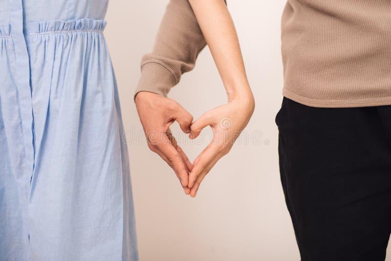 Giovani coppie che si tengono per mano nella forma di cuore fotografie stock libere da diritti