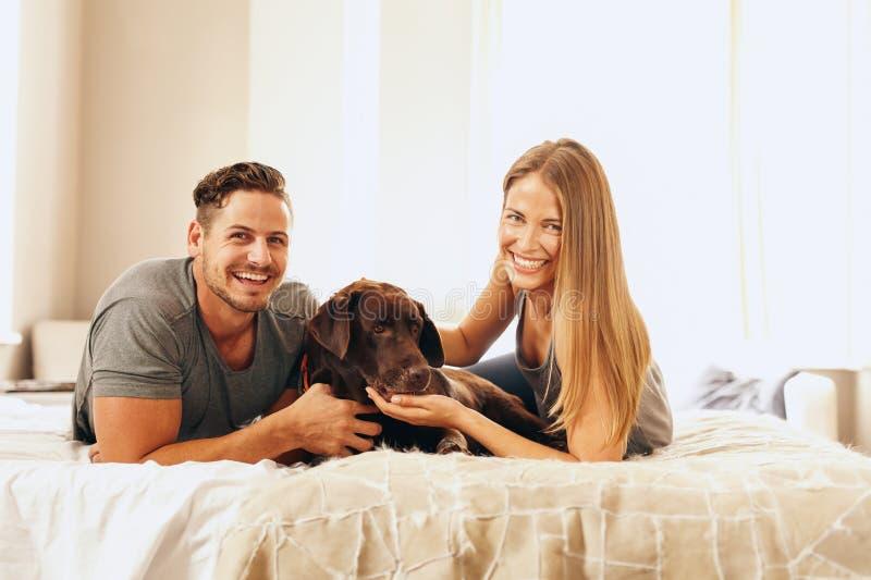 Giovani coppie che si trovano sul letto con il loro cane fotografia stock