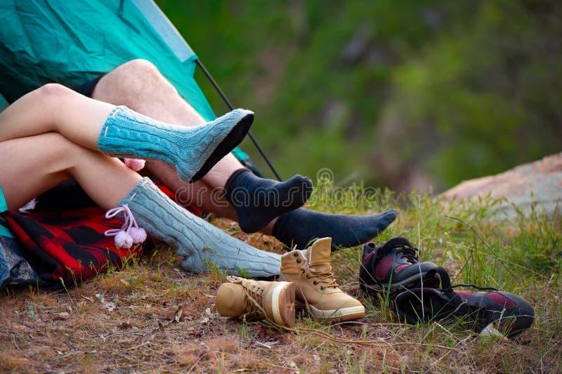 Giovani coppie che si trovano in una tenda Piedi delle viandanti di menzogne Campeggio, tra fotografia stock libera da diritti