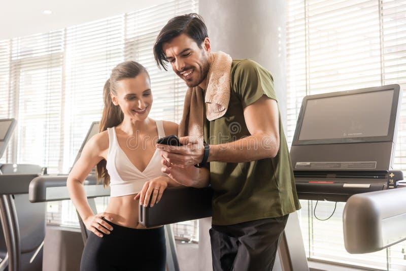 Giovani coppie che sorridono mentre comunicando sul dur del telefono cellulare fotografie stock