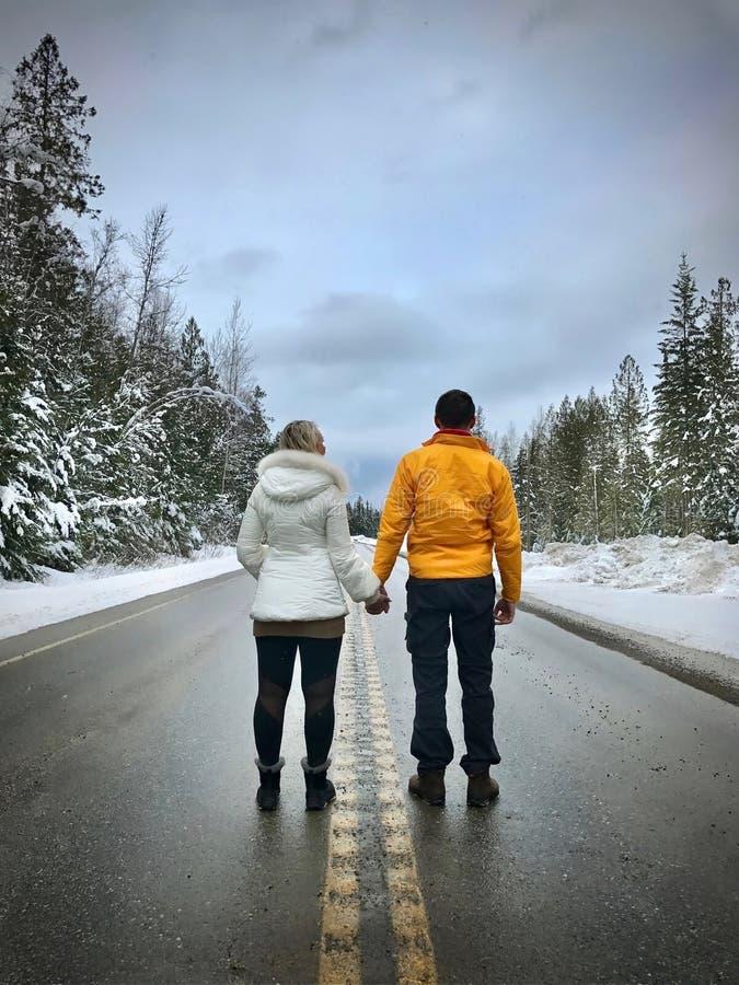 Giovani coppie che stanno sul tenersi per mano della strada Persone appena sposate vicino a Revelstok Columbia Britannica canada immagine stock libera da diritti