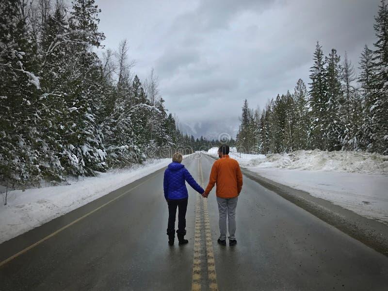 Giovani coppie che stanno sul tenersi per mano della strada Persone appena sposate vicino a Revelstok Columbia Britannica canada fotografia stock