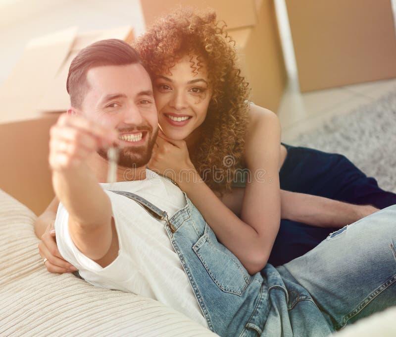 Giovani coppie che tengono la chiave ad un nuovo appartamento fotografie stock