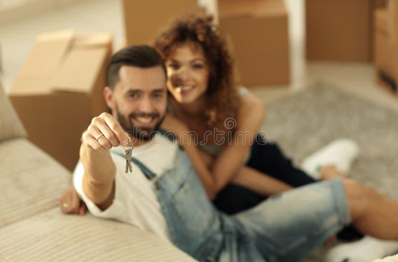 Giovani coppie che tengono la chiave ad un nuovo appartamento fotografie stock libere da diritti