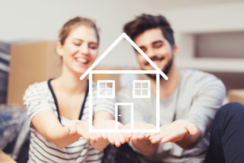 Giovani coppie che tengono la loro nuova, casa di sogno in mani fotografie stock libere da diritti
