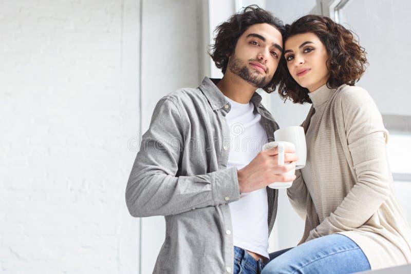 giovani coppie che tengono le tazze di caffè e che esaminano macchina fotografica immagini stock libere da diritti