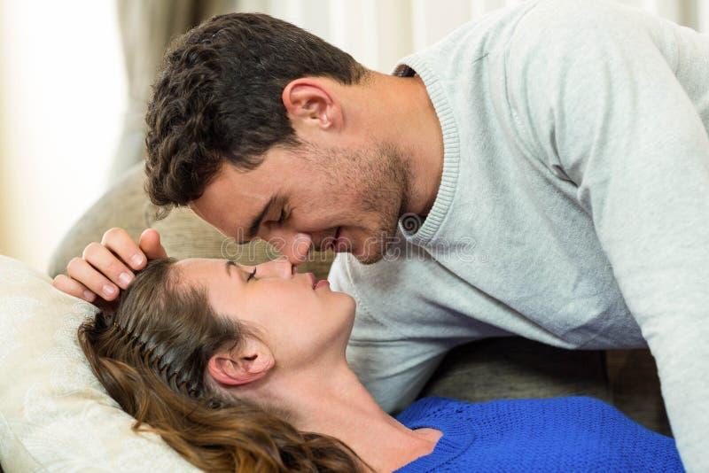 Giovani coppie circa da baciare sul sofà fotografia stock libera da diritti
