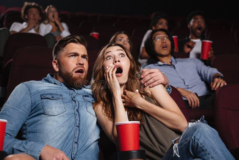 Giovani coppie colpite che guardano un film horror fotografie stock
