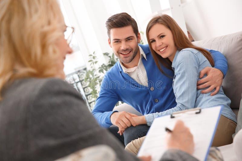 Giovani coppie con abbracciare di terapia familiare dello psicologo felice immagini stock libere da diritti