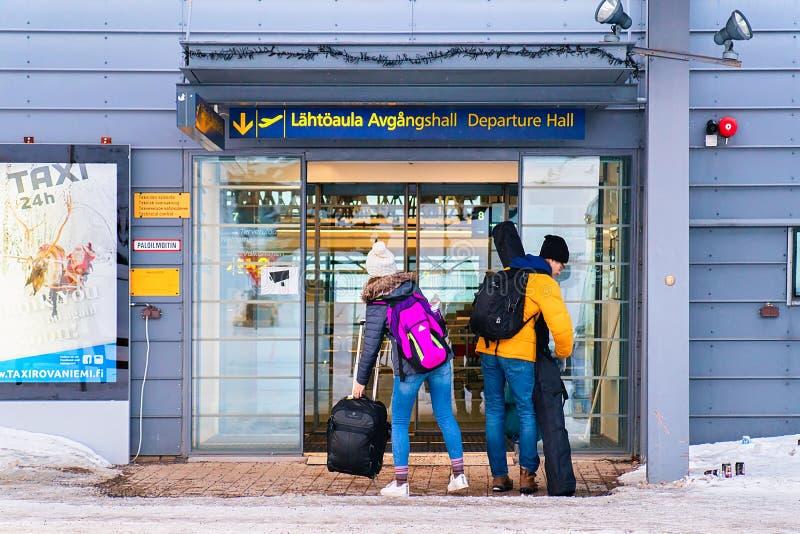 Giovani coppie con bagagli all'entrata nell'inverno dell'aeroporto di Rovaniemi fotografie stock