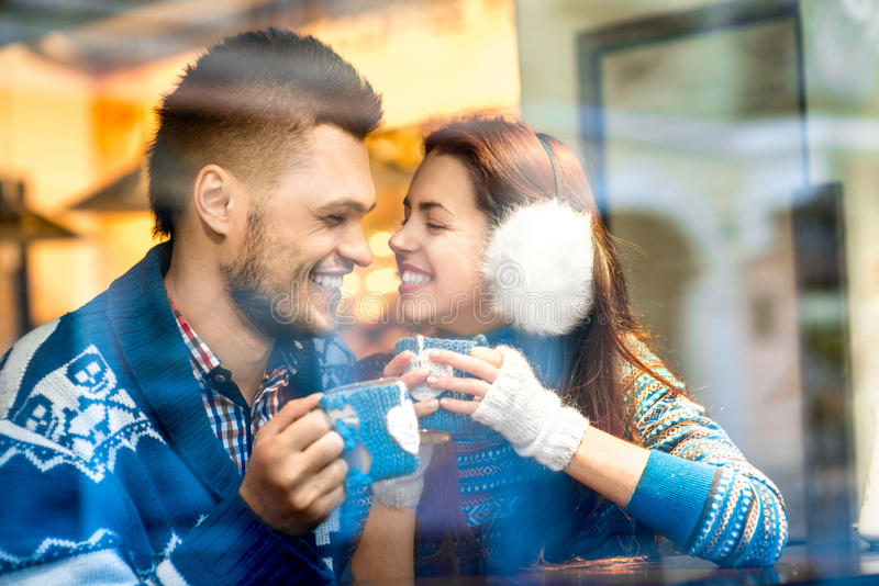Giovani coppie con caffè al caffè nell'inverno fotografie stock libere da diritti