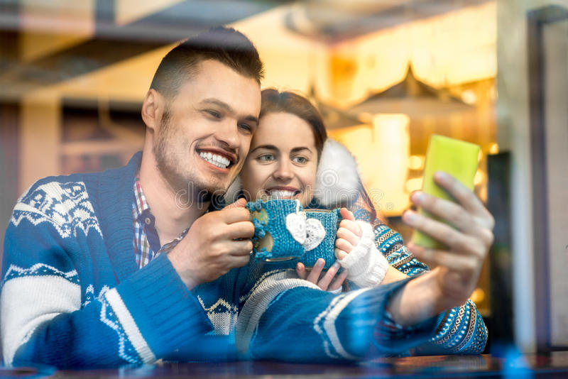 Giovani coppie con caffè al caffè nell'inverno fotografia stock libera da diritti
