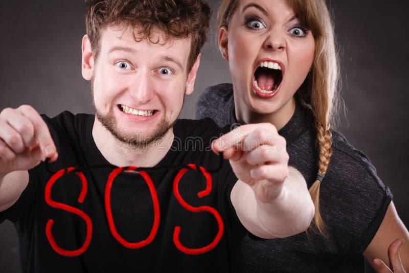 Giovani coppie con cuore rotto e la parola di SOS fotografie stock